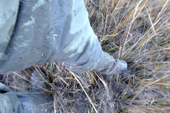 looking down on very muddy pants and footware