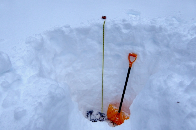 Snow shovel in deep snow next to measuring tape. Tape is 65 inches long.