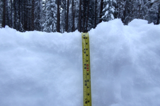 measuring tape in snow. Numbers at top of snow level read 65 inches or 166 centimeters.