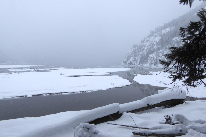 snow covered mud flats and steep mountainside