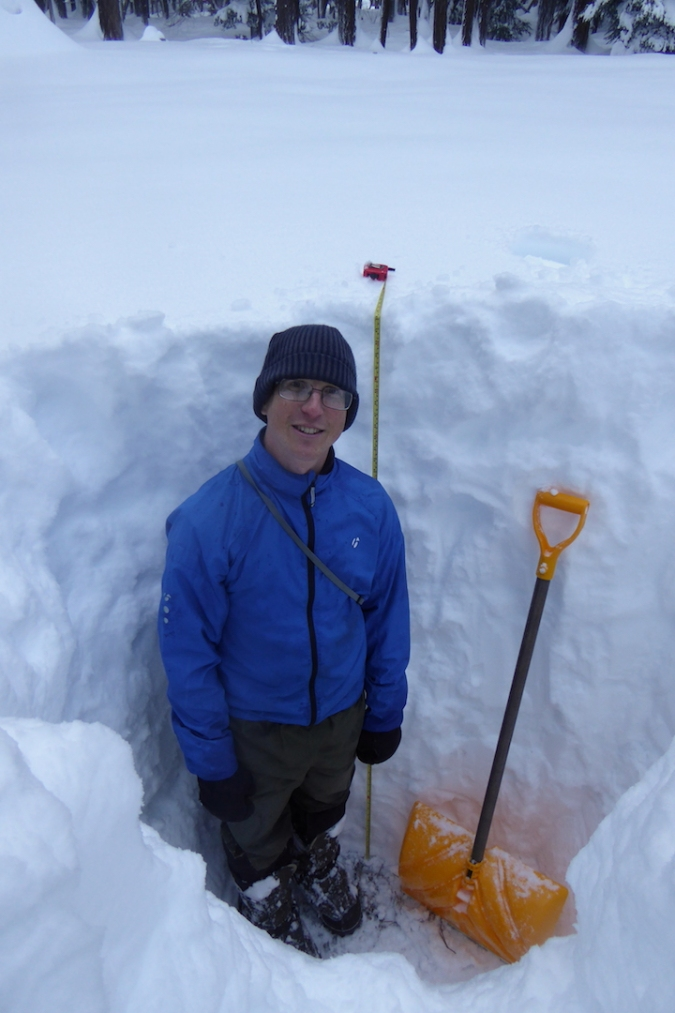 Person standing in deep snow pit. Pit is 65 inches deep.
