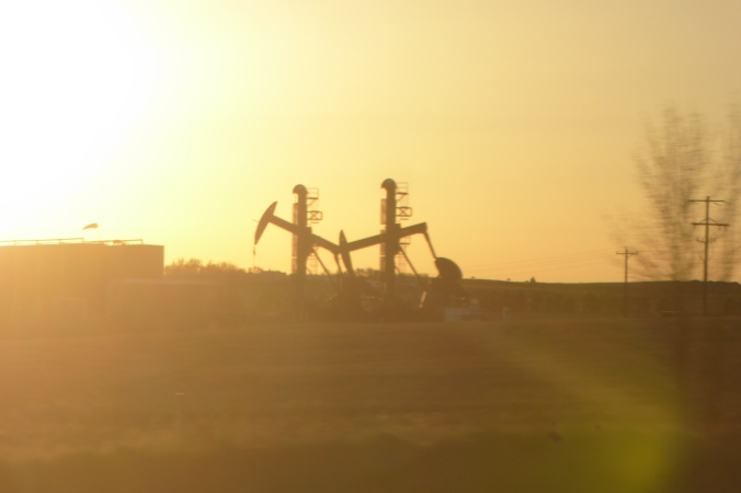 oil wells silhouetted by the setting sun