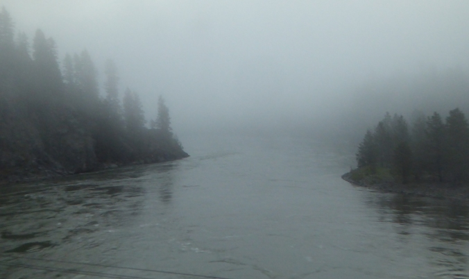 river flowing through foggy valley