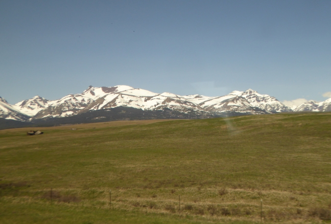 rolling prairie with snow-capped mountains in background