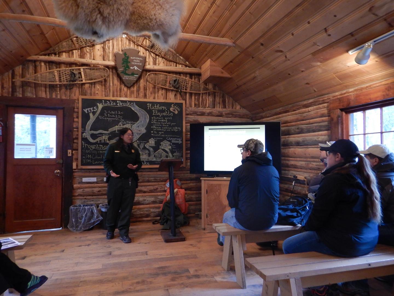 Ranger in log cabin talking to people