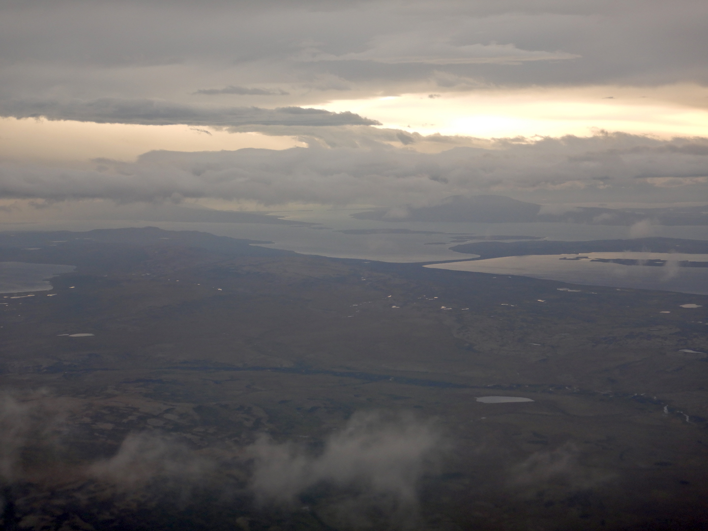 Aerial view of land, lake, and clouds.
