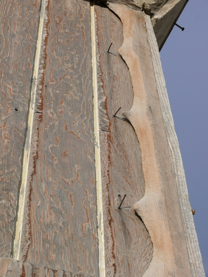 scalloped edge of wood and nails on building