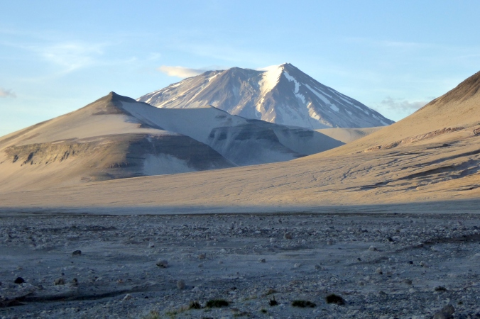 pumice covered landscape with volcano in background