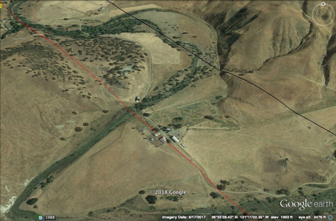 Google Earth image of creek valley with buildings at center.