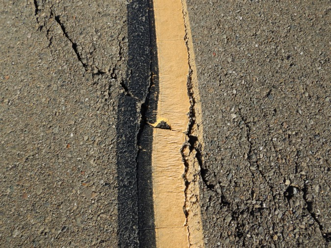 Crack in pavement across yellow line.