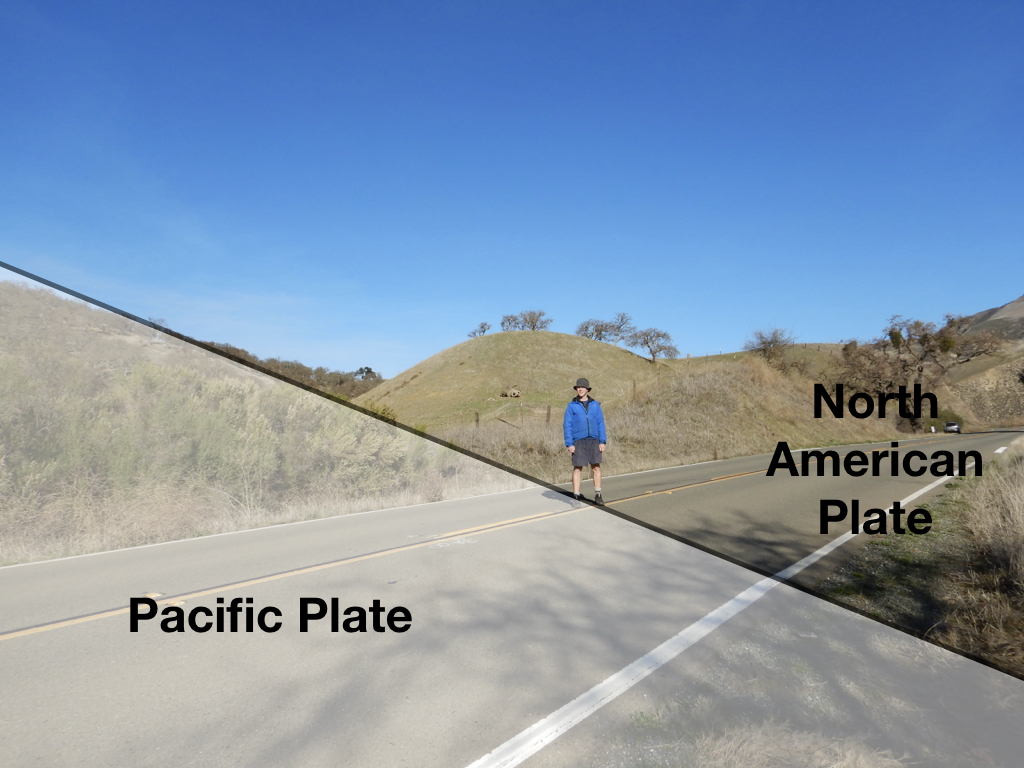 Person standing on road. Land to right is North American plate. Land on lower left is Pacific plate.