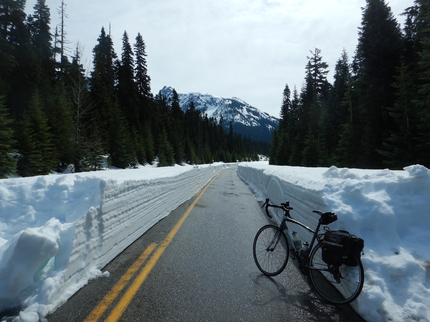 bicycle leaning against snow bank with one lane of plowed highway