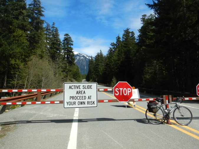 "gate across highway. sign reads ""Active slide area proceed at your own risk"" and ""Stop"""