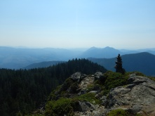 view of mountains and forest with tall rock cairn a lower right