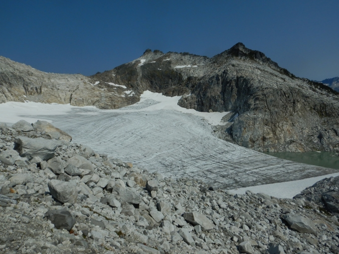 small, mostly snow free glacier tucked in a basin below a mountain peak