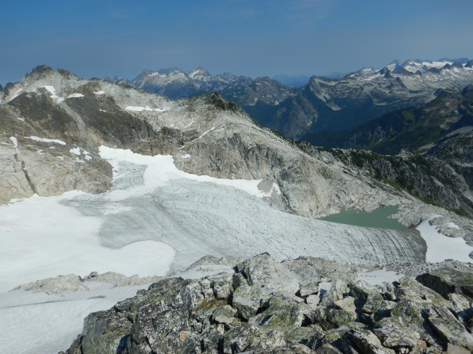view of glacier in mountain basin. Snow covered mountains on horizon.
