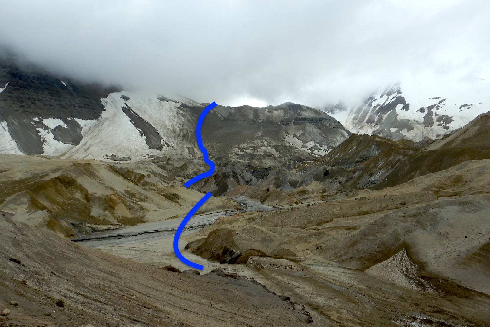 View of hummocky landscape created by ash and pumice covered glaciers at the foot of mountains hidden in clouds. Blue line near center represents route.