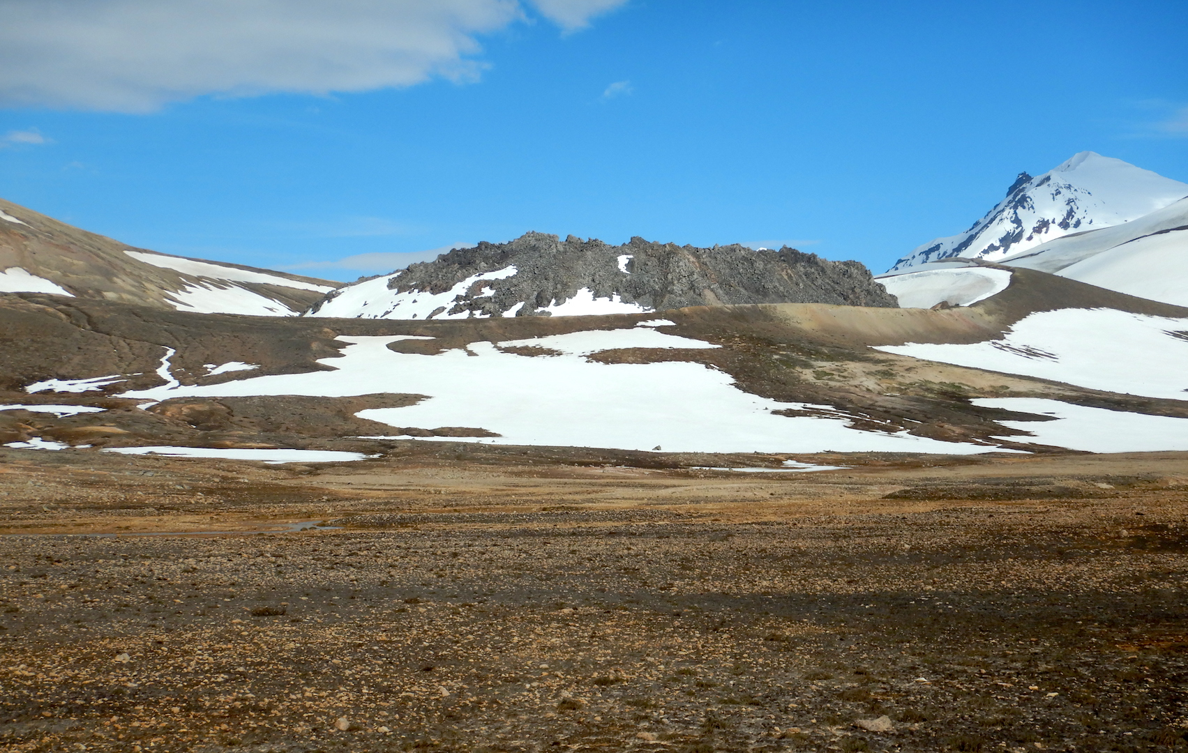 view of pumice-covered flats and snow fields dark-colored lava dome at center