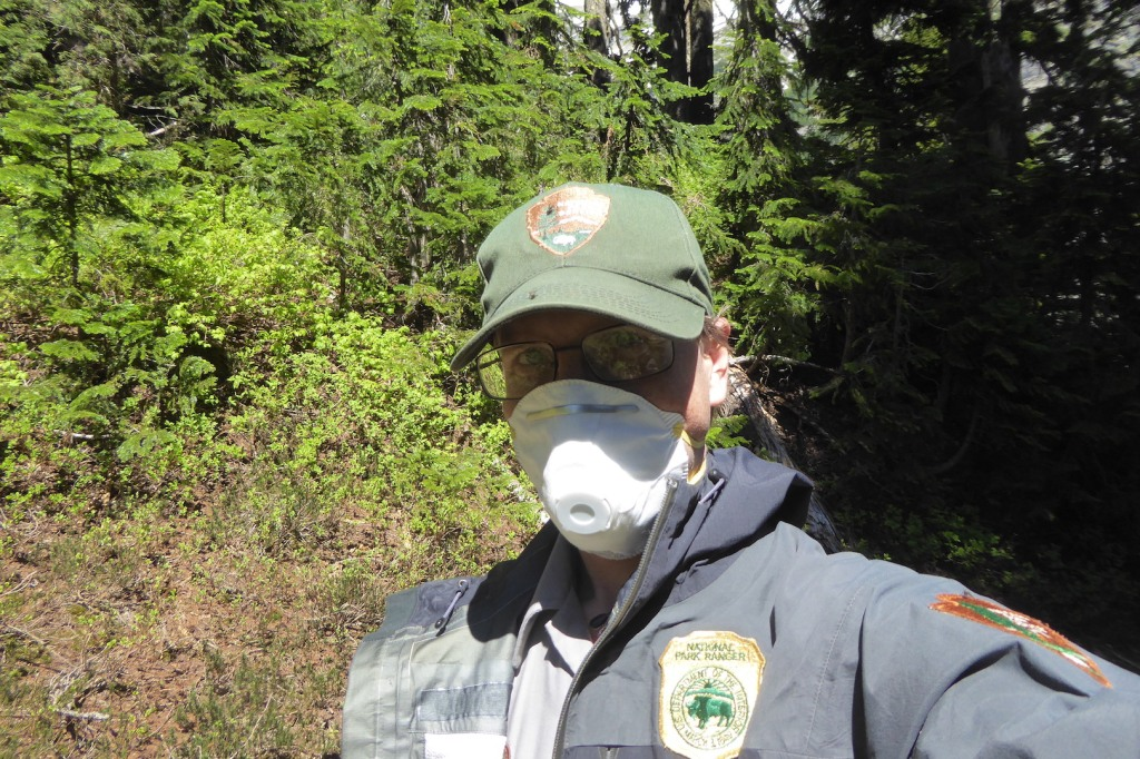 Selfie of ranger wearing NPS hat, black coat, and N95 mask