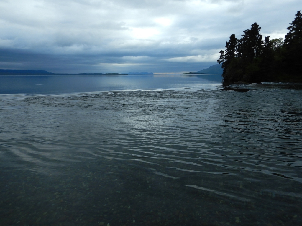 view of lake and shallow river on overcast day. Water flow is toward photographer and to right.