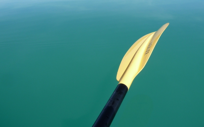 turquois colored lake water. A yellow kayak paddle with a black handle offers contrast