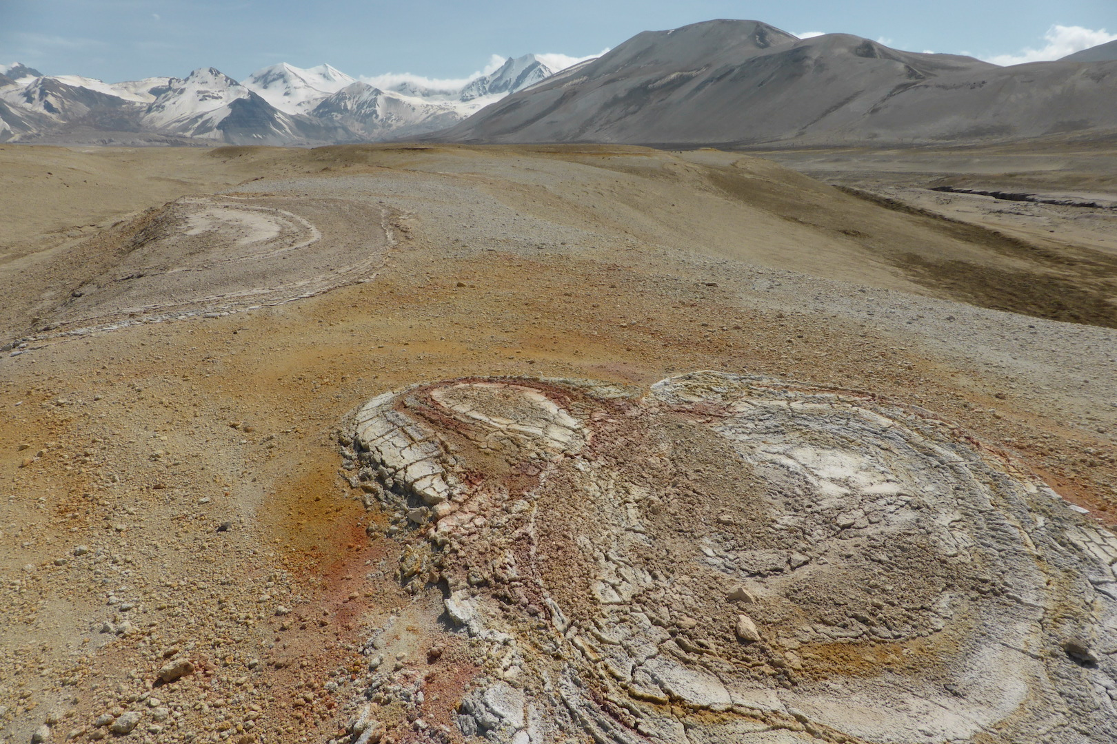 ovoid crusts of clay (lower right) lay on top of gray, orange, and brown pumice fields. snow covered mountains
