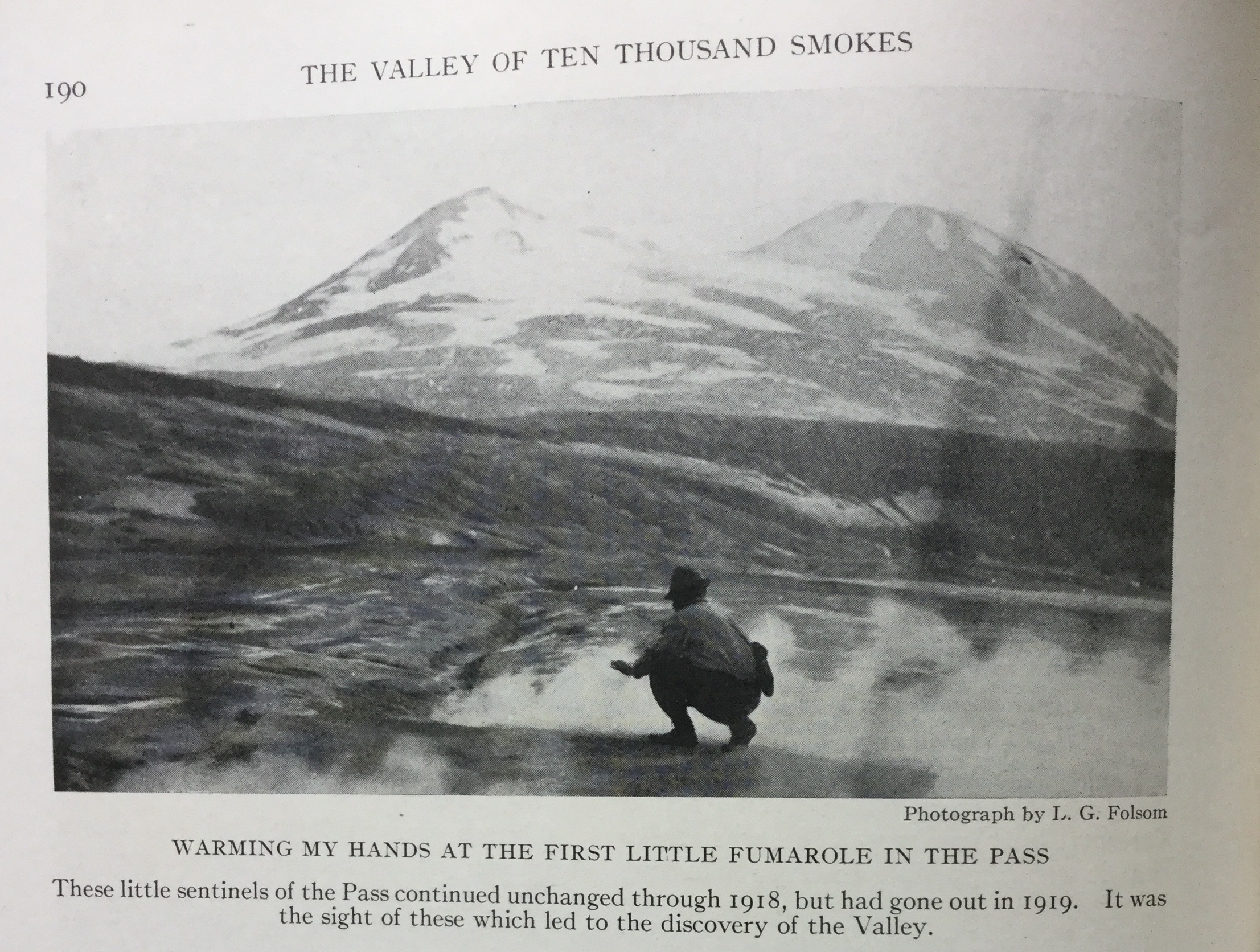 """black and white photo. man squats at center next to small steam vent. a snow capped mountain is o the horizon. text reads """"190. The Valley of Ten Thousand Smokes. Photograph by L. G. Folsom. Warming my hands at the first little fumarole in the pass. These little sentinels of the Pass continued unchanged through 1918, but had gone out in 1919. It was the sight of these which led to the discovery of the Valley."""""""