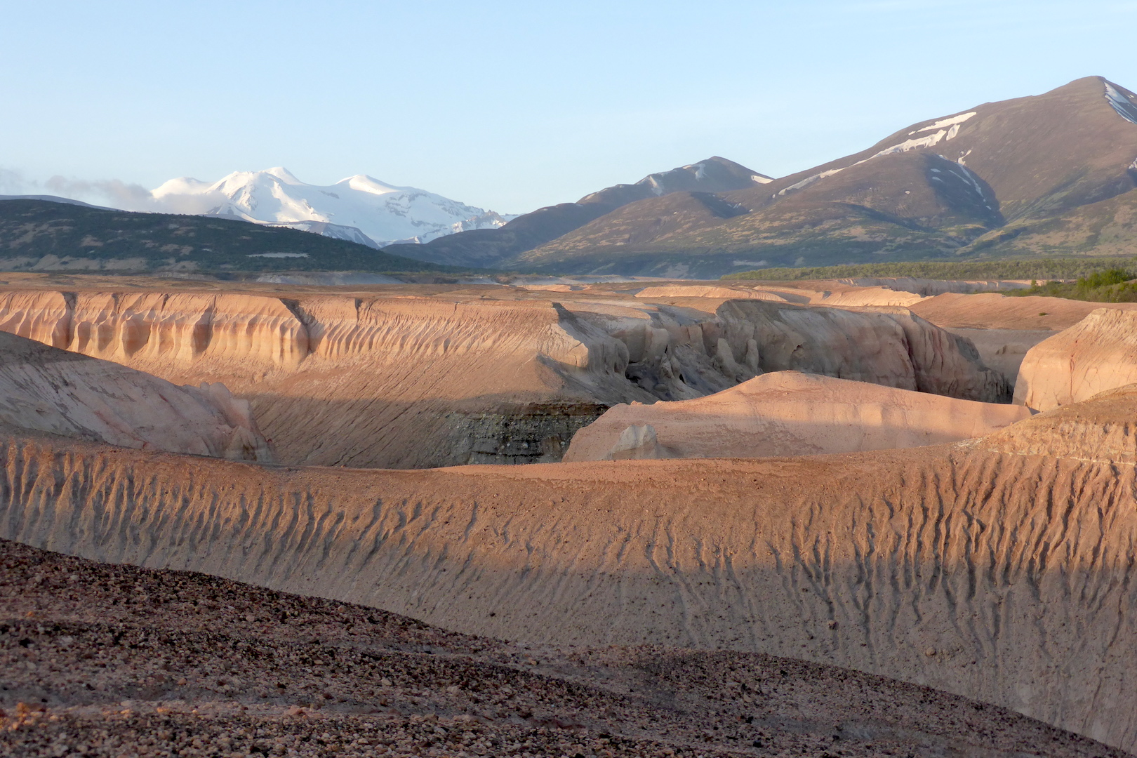 canyons carved through pumice and ash on lower half of photo. mountains line horizon. low angled sunlight highlights depth of canyons